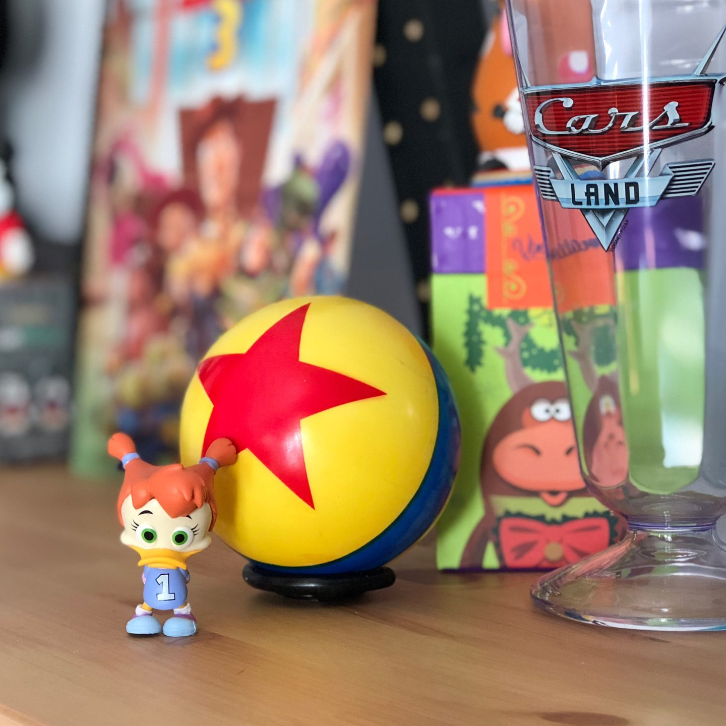 A figure of Gosalyn from Darkwing Duck is sat on a shelf surrounded by items like a Luxo Ball and Pixar Cars merchandise