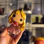 A Sleeping Beauty glitter funko pop in focus, with a blurred background of fairy lights and polaroids hanging up.