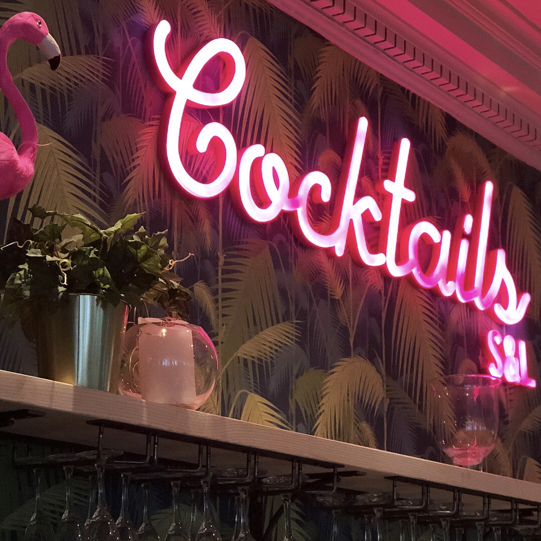 A palm tree wallpapered wall featuring a neon sign saying Cocktails in swirly script writing