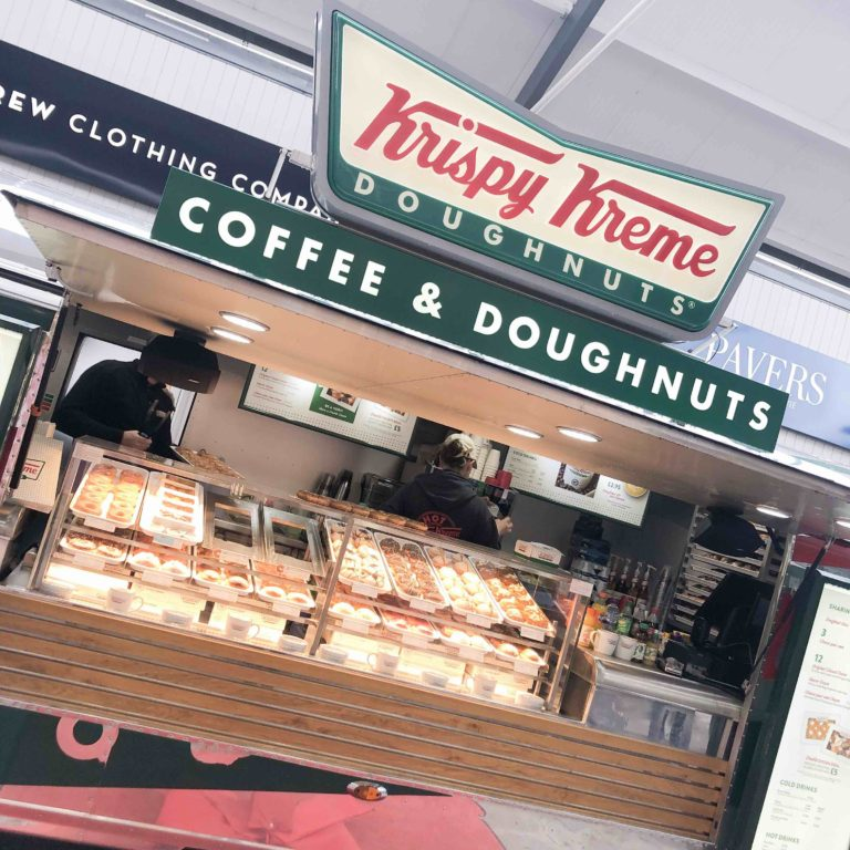 A photo of the chrome trailer, with the Krispy Kreme logo above. All of the doughnuts on display and friendly team members busy.
