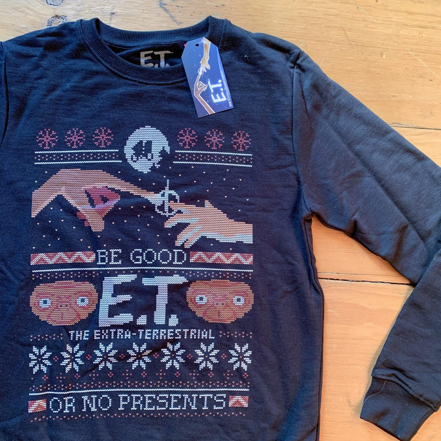 A nevy blue christmas jumper featuring ET The Extra Terrestrial.