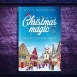 A paperback copy of Christmas Magic at the Tenby Crystal Shop by Kelly Matthews on a purple background. The cover has a snow covered village on the front