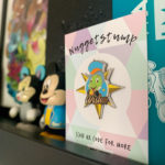 A shelf featuring one of my items from my etsy store. A jiminy cricket enamel pin.