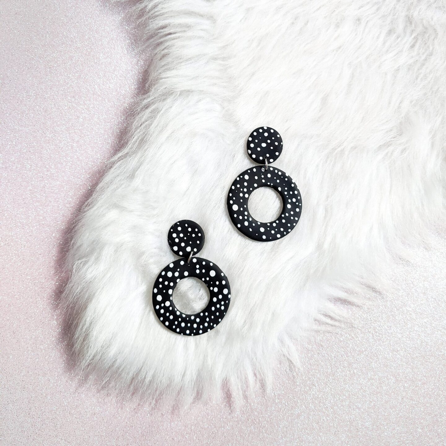 A photo of black and white polka dot dangly earrings on a faux fur rug
