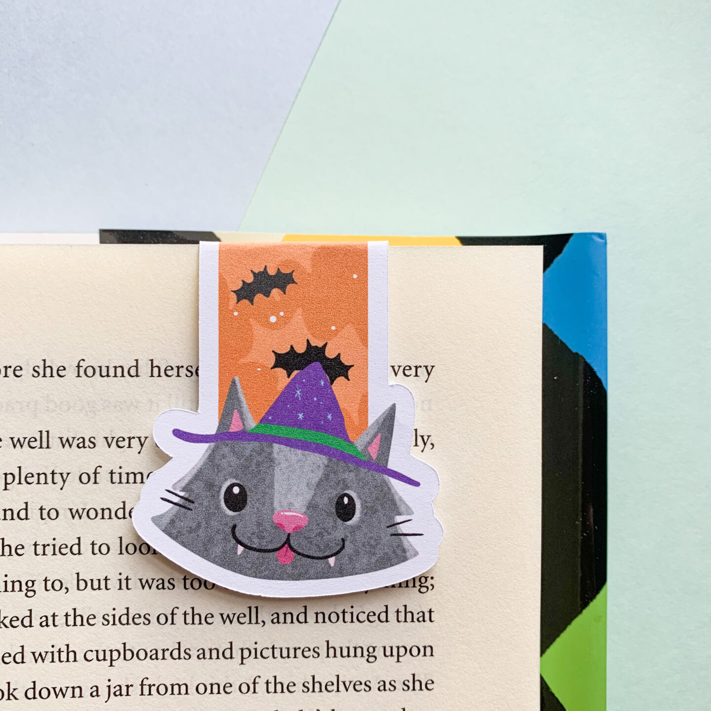 A witches cat illustration which has been turned into a magnetic bookmark. Clipped onto a page in a book.