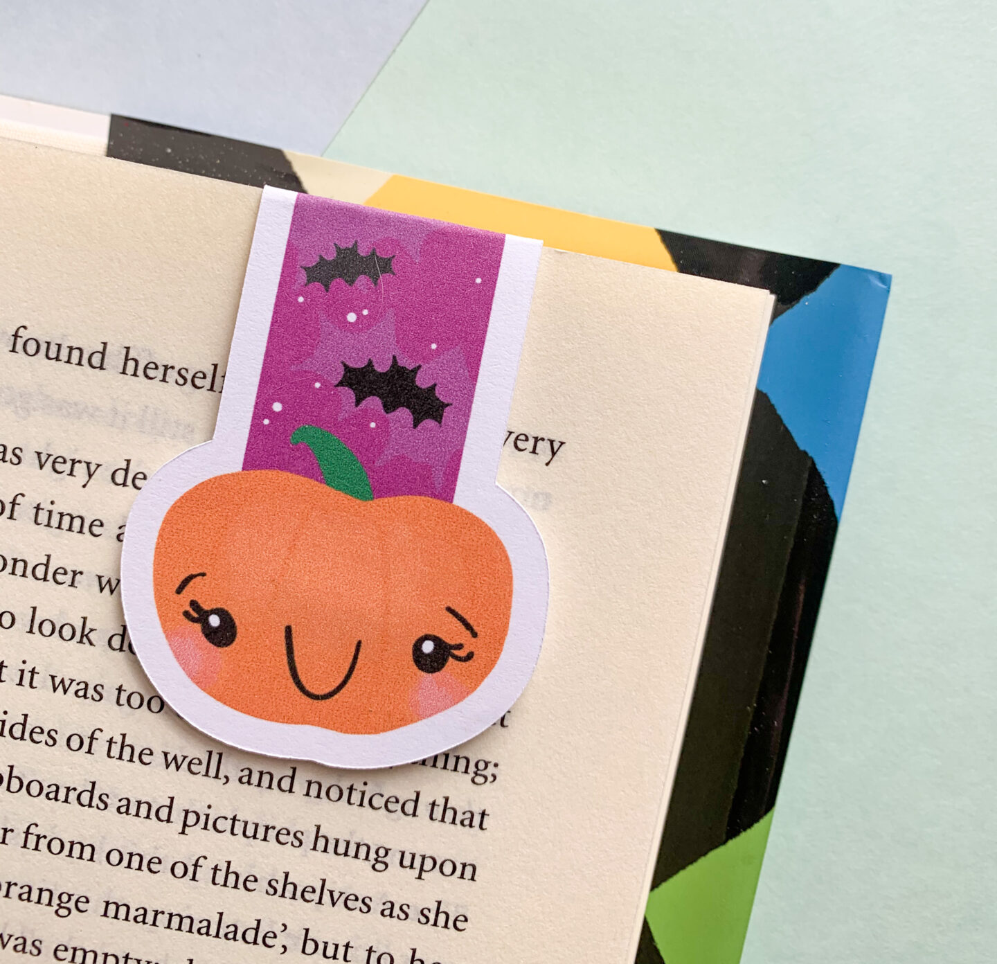 A cute pumpkin magnetic bookmark hanging off a page in a book.