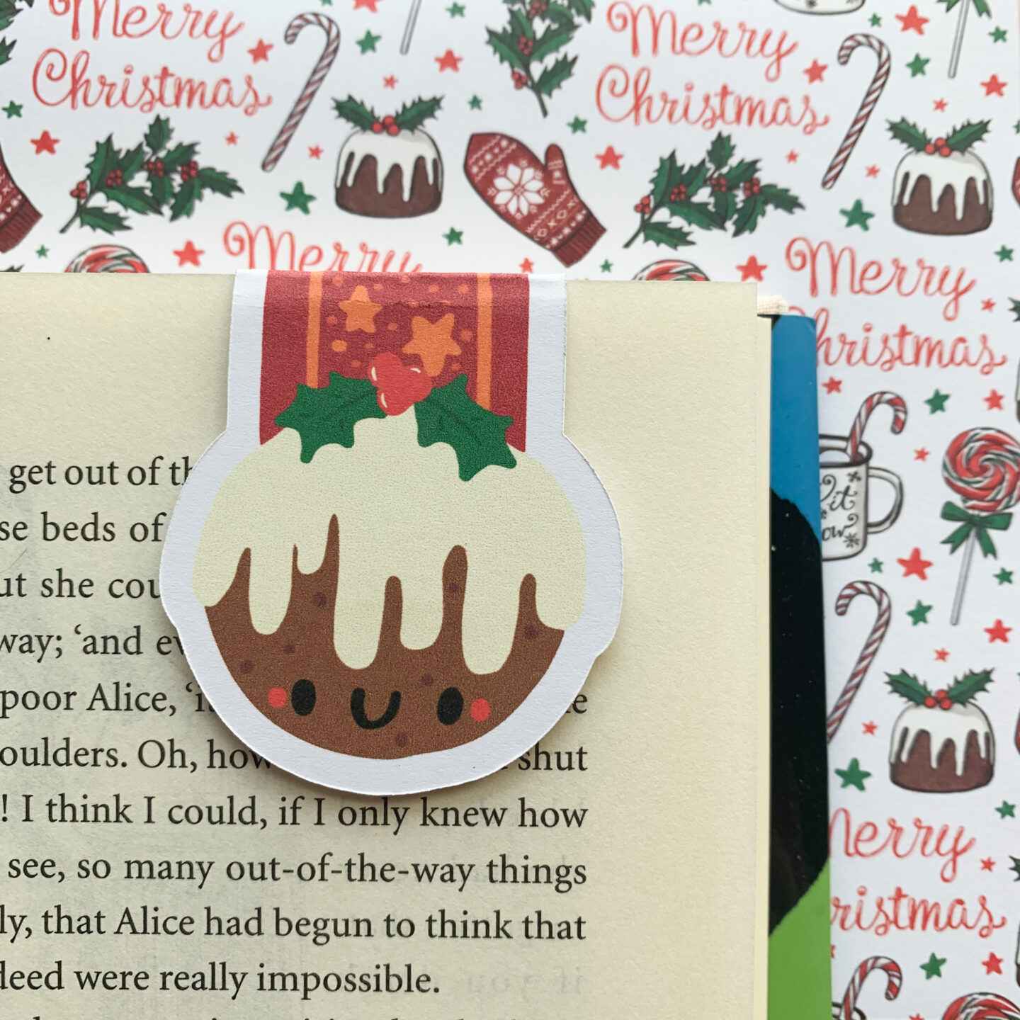 A Christmas Pudding magnetic bookmark hanging onto a book